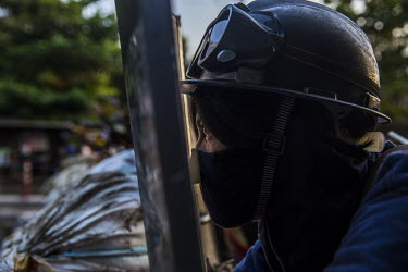 An anti-coup protestor peers through a slit in a homemade shield as security forces approach their road block.