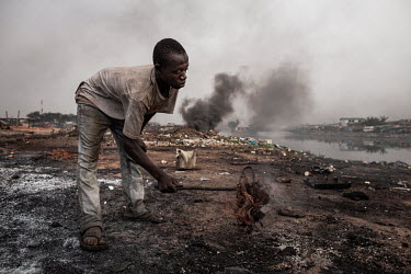 A boy burns cables from computers and other electronic equipment in order to retrieve copper, at Agbogbloshie dump, which has become a dumping ground for computers and electronic waste from all over t...