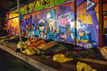 A row of people sleeping rough on the wooden terrace of a play area, decorated by a grafitti artist.