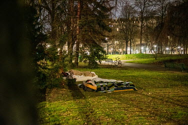 Homeless people sleeping in the Parc des Bastions in the city centre, on a cold winter night.