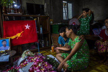 Ma Hnin Wai Oo and her 15-year-old son Chit Min Aung mourn beside the dead body of Ko Aung Aung Zaw (41), a trishaw driver who was shot in the head and killed the previous evening while guarding his n...