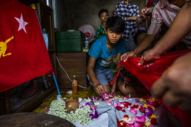 Chit Min Aung (15) places flower petals on the dead body of his father Ko Aung Aung Zaw (41), a trishaw driver who was shot in the head and killed the previous evening while guarding his neighbourhood...