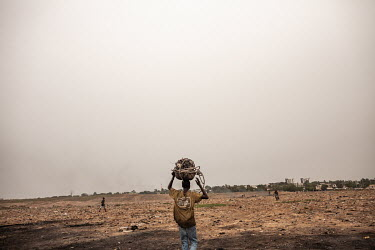 A boy carries electrical cables to a burning site at Agbogbloshie dump, which has become a dumping ground for computers and electronic waste from all over the developed world. Hundreds of tons of e-wa...