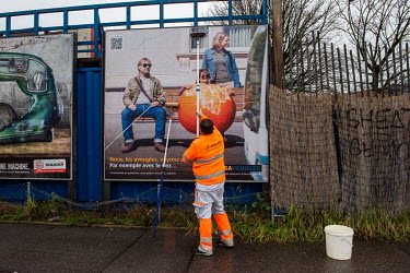 A man in an orange high visibility uniform putting up an advertising poster for an organisation supporting people with restricted vision.