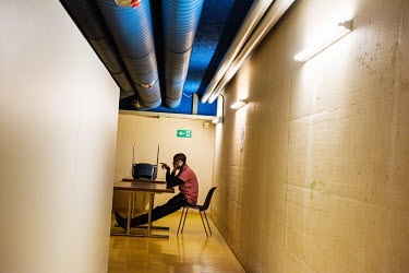 A homeless man makes a mobile phone call as he sits in a hallway at a winter emergency shelter, run by the Ville de Geneve, in an abri PC (a civil defence shelter, an underground nuclear bunker).