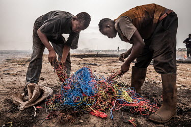 Boys sort through electrical cables at a burning site at Agbogbloshie dump, which has become a dumping ground for computers and electronic waste from all over the developed world. Hundreds of tons of...