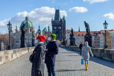 A couple with face masks look at the city while walking on the Charles Bridge. On 1 March 2021 the state of emergency lockdown in the Czech Republic was reinstalled because of the fast increasing numb...