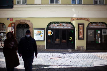 A woman without a face mask and her companion wearing his below his nose as they walk past a closed restaurant on Karlova Street. On 1 March 2021 the state of emergency lockdown in the Czech Republic...