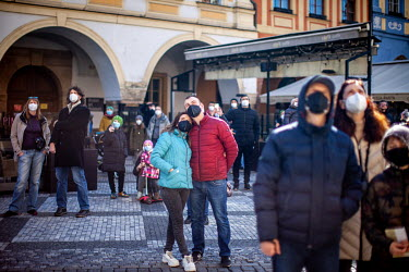 A small crowd looking at The Prague Astronomical Clock or Prague Orloj, a medieval astronomical clock on the Old Town Hall in the Old Town Square. On 1 March 2021 the state of emergency lockdown in th...