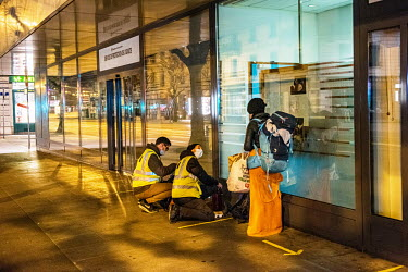 A member of an emergency winter night team, social workers from the Ville de Geneve, on a late night outreach tour in support of homeless people, talks to a homeless woman. A team goes out every night...