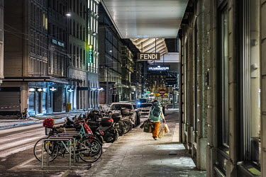 A homeless woman with her belongings, seeking a place to pass the night, walks along the Rue du Rhone, one of Geneva's principal luxury shopping streets. The temperature is approx -4C and snow remains...