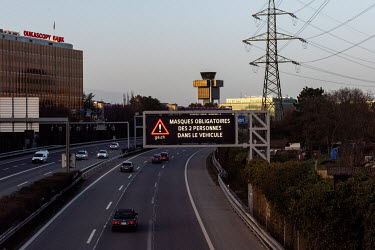 A digital sign over the motorway passing Geneva Cointrin airport, warning that face masks are obligatory as soon as there are two people sharing a car.
