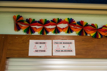 A sign in English and French that reads: No Mask = No Food, at the food counter in a winter emergency shelter for the homeless run by the Ville de Geneve in an abri PC (a civil defence shelter, an und...