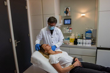 Dr Herve Raspaldo at the Imaderm Clinic prepares to treat his client, Emilie, with injections of hyaluronic acid fillers. Emilie says she is doing this partly to feel better on Zoom, which due to the...