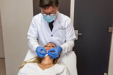 Dr Herve Raspaldo, at the Imaderm Clinic, manipulates the chin of his client, Emilie, after giving her injections of hyaluronic acid fillers. Emilie says she is doing this partly to feel better on Zoo...