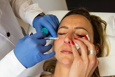 Dr Herve Raspaldo, at the Imaderm Clinic, treats his client, Emilie, with injections of hyaluronic acid fillers. Emilie says she is doing this partly to feel better on Zoom, which due to the pandemic...