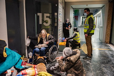A member of an emergency winter night team, social workers from the Ville de Geneve, on a late night outreach tour in support of homeless people, gives out hot drinks to a group of drug users, camped...