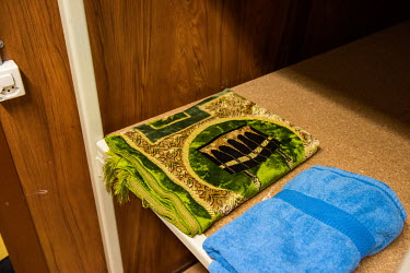 A prayer mat amongst other items for use by homeless people at a winter emergency shelter run by the Ville de Geneve in an abri PC (a civil defence shelter, an underground nuclear bunker).