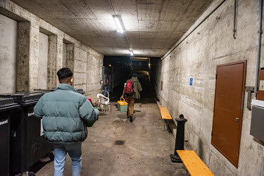 Social workers, carrying containers of hot food and drinks, head out on outreach in support of homeless people, leaving an underground winter shelter run by the Ville de Genève in an abri PC (a civil...