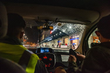Members of an emergency winter night team, social workers from the Ville de Geneve, drive to the main railway station while on a late night outreach tour in support of homeless people in the town.
