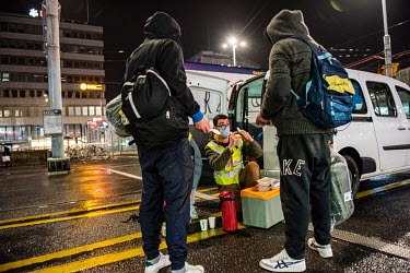 The emergency winter night outreach team, social workers from the Ville de Geneve shelter, giving out food, drink and sleeping bags to homeless men outside Geneva main station.