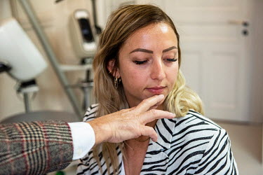 Emilie, a client of Dr Herve Raspaldo, in discussion with the doctor before receiving cosmetic face enhancement injections using hyaluronic acid fillers. She says she is doing this partly to feel bett...
