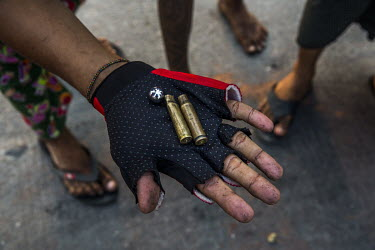 An anti-coup protestor holds bullet casings and a metal ball shot by the security forces as they cracked down on demonstrations in the Hlaingtharyar industrial zone on the outskirts of Yangon.