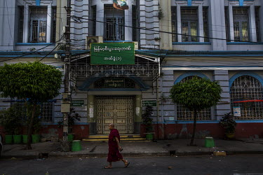 A Buddhist monk walks past the closed doors at the main entrance of Myanma Economic Bank Branch No.1 where many of the staff have joined the Civil Disobedience Movements and are staying away from thei...