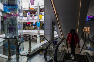 A member of staff walks up an escalator that has been turned off in a shopping centre where, as a result of the military coup and the suppression of protests, most of the shops are closed and the cent...