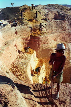 A team of men digging a claim by hand in a saphire mine. The discovery of one saphire under a road bridge led to an influx of prospectors and the growth of a village to support saphire mining in the a...