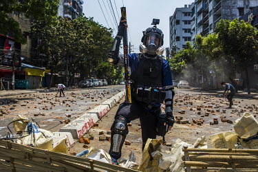 Soe Win Naing (26), wearing makeshift armour and holding a firework launcher, stands behind a makeshift barricade during an anti-coup protest. Behind him youths scatter bricks on the road to try an im...