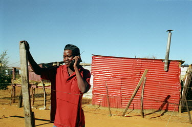 A man talking on his mobile phone in the Kagiso informal settlement.