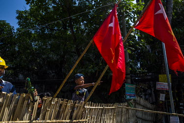 A young anti-coup protestor points to the security forces while standing behind a makeshift barricade where two National League for Democracy (NLD) flags hang from bamboo poles.
