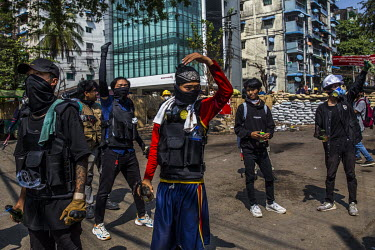 Anti-coup protestors, armed with molotov cocktails, wait to confront the security forces behind a makeshift barricade.