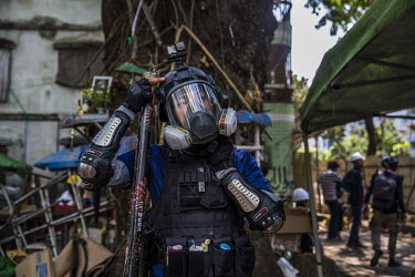 Soe Win Naing (26), wearing makeshift armour and holding a firework launcher, stands behind a makeshift barricade during an anti-coup protest.