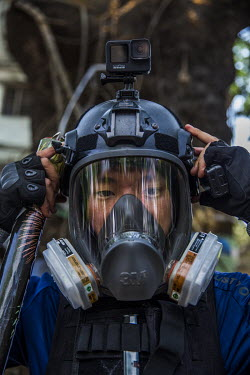 Soe Win Naing (26), wearing makeshift armour with a camera mounted on his helmet and holding a firework launcher, stands behind a makeshift barricade during an anti-coup protest.