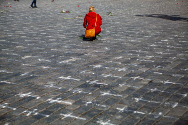 A woman squats beside flowers laid along with 25,000 white crosses chalked on the ground in the Old Town Square. Each cross symbolises the death of a person from COVID-19. The number of victims since...