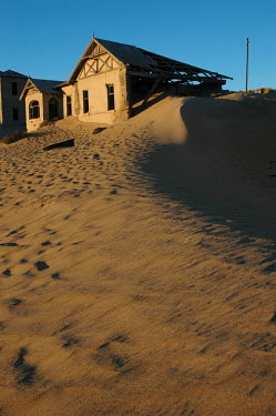 Sand slowly overwhelming an old abandoned house. Kolmanskop, an old diamond mining town 10 km outside Luderitz, is slowly being drowned by sand dunes from the surrounding desert. The diamond rich sand...