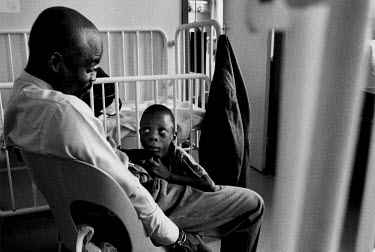 A boy, too weak from AIDS to stand for long, holds onto his father's legs as they share a brief moment during a visit to teh Cotlands Baby Sanctuary.