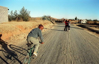 A boy rides bicycle along an unpaved rural road.