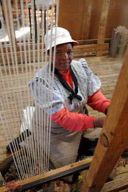 A womaning weaving on a hand loom at a rural weaving co-operative.