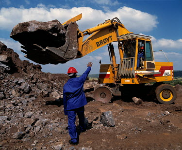 A worker signals to the operator in a front end loader atan open cast mine.