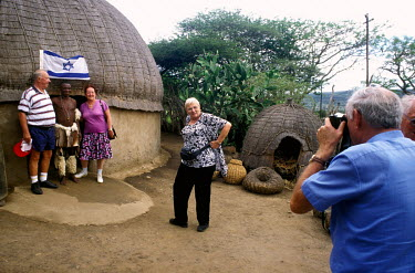 Israeli tourists pose with a Zulu man during a visit a traditional Zulu village.