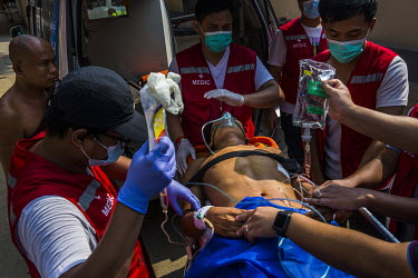 Volunteer medics unload a protestor injured by a gunshot wound from an ambulance at a hospital where they hope he will be able to get treated.