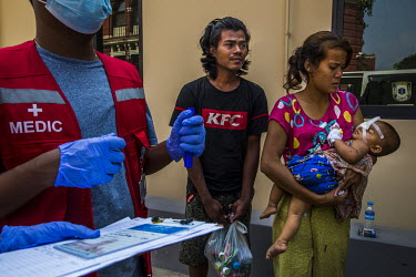 Moe Moe Khine, the mother of one year old Thin Thawdaw Tun, holds her injured daughter who was shot in the eye with a rubber bullet fired by the security forces, while the baby was inside the family h...