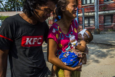 Moe Moe Khine, the mother of one year old Thin Thawdaw Tun, and Nay Win Tun the child's father, carry their injured daughter who recieved treatment from volunteer medics after she was shot in the eye...