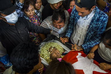 Family members mourn beside the body of 15-year-old Aung Kaung Htet, who died after being shot in the face the previous day while protesting the coup in his neighbourhood in Tharketa township where th...