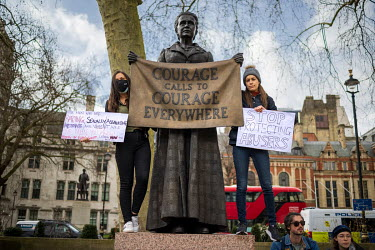 Two women, standing on the plinth of Suffragette Millicent Garrett Fawcett's statue in Parliament Square, holding placards with slogans referencing sexual abuse of women while taking part in a 'Freedo...
