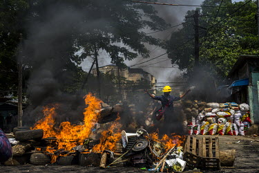 Anti-coup protestors burn tyres to block a road to prevent the security forces from entering into their neighbourhood in Hlaing township.