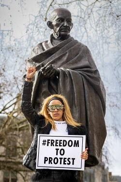 A woman, standing beside the Mahatma Gandhi statue in Parliament Square, raises her fist while holding a placard with the slogan 'Freedom to Protest' during a demonstration against Home Secretary Prit...